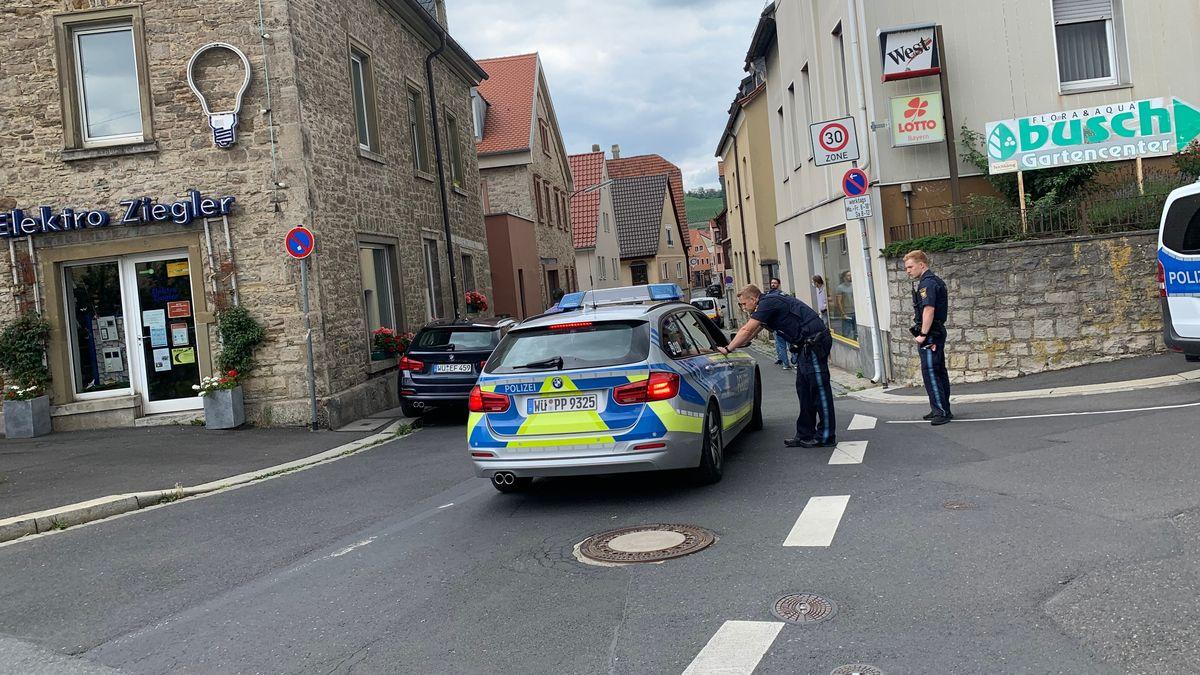 Polizisten und Streifenwagen vor dem überfallenen Lottogeschäft in Würzburg-Heidingsfeld