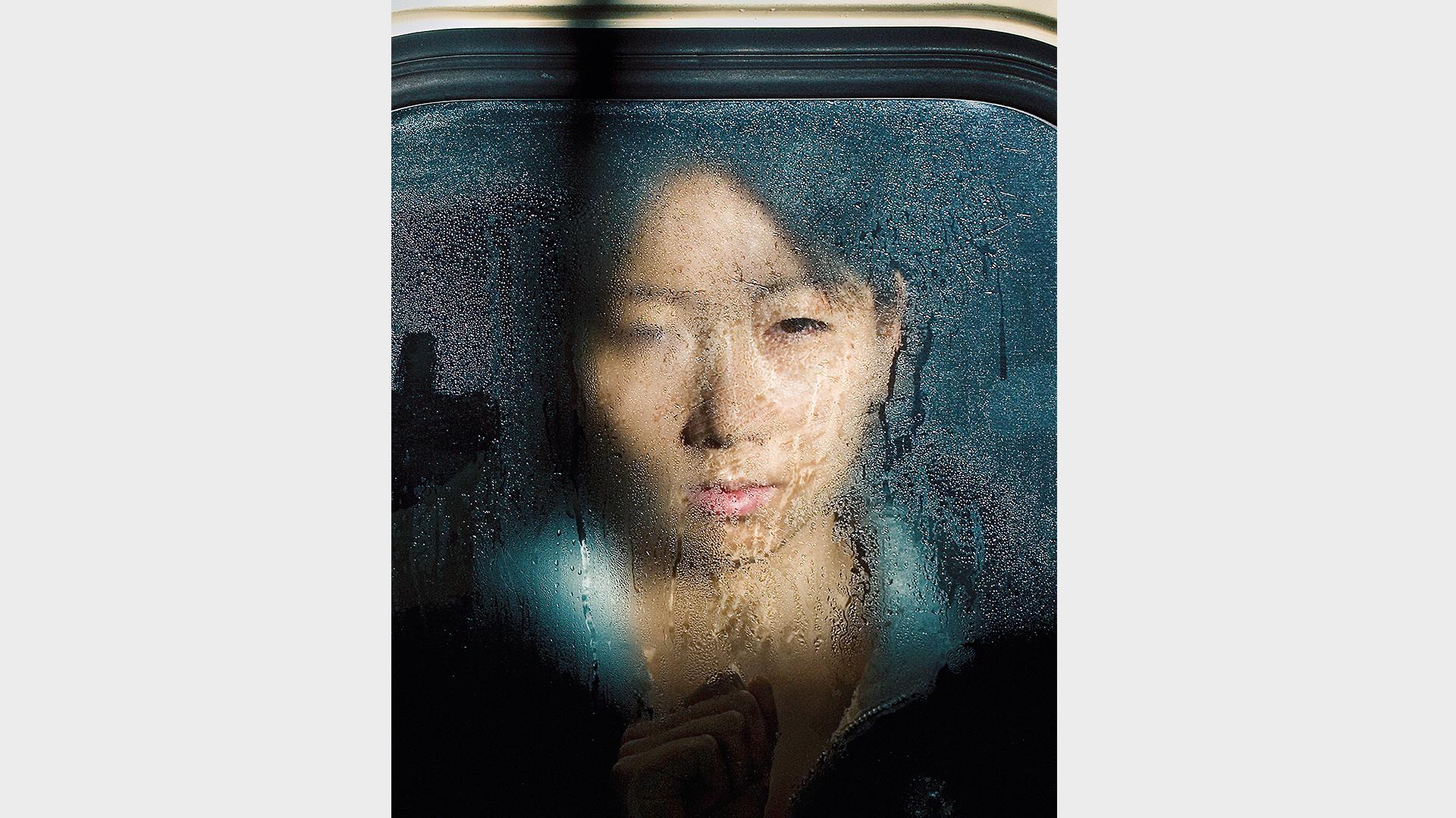 Eine junge Chinesen hinter einer beschlagenen Glasscheibe eines Zuges in Tokyo, mit der rechten Hand wischt sie leicht durch das Kondenswasser an der Scheibe.