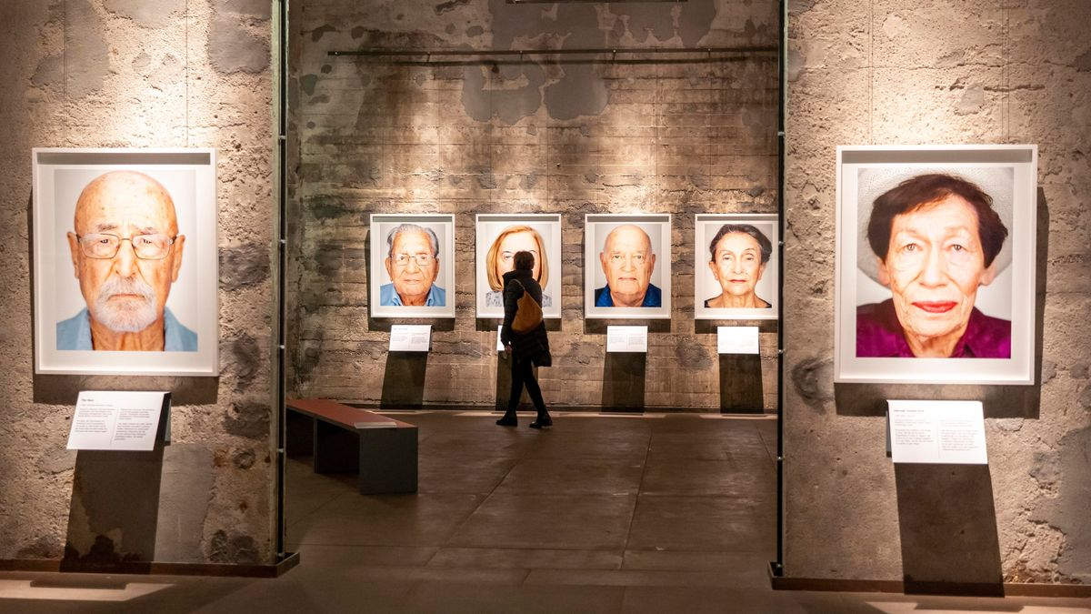 An fleckigen Betonwänden hängen großformatige gerahmte Porträtaufnahmen von Holocaust-Überlebenden