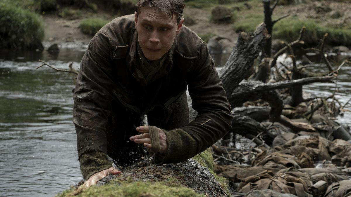 Ein erschöpfter britischer Soldat des Ersten Weltkriegs überquert kriechend auf einem Baumstamm einen Fluss