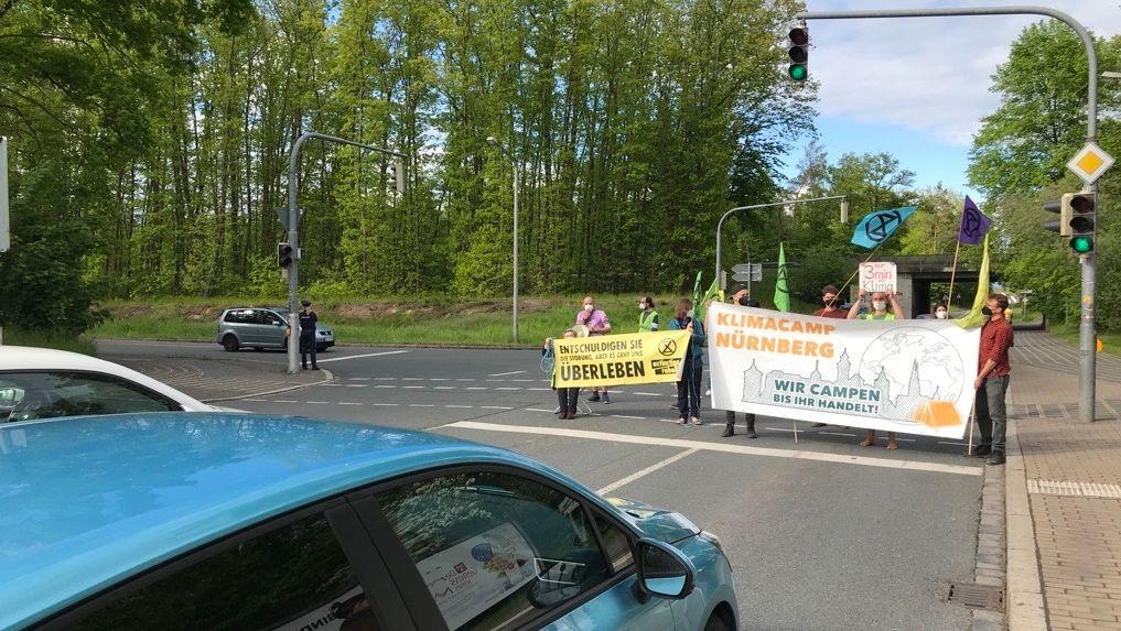 Demonstranten mit Transparenten blockieren eine Straße. Davor warten Autos.