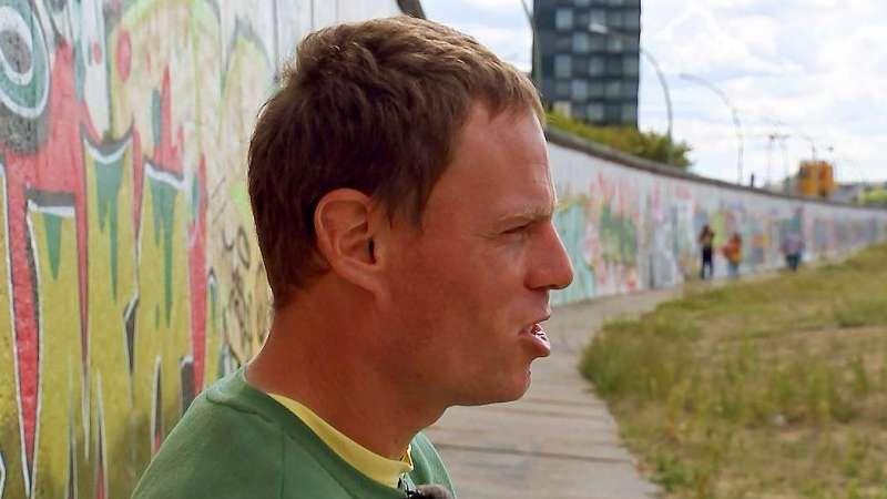 Ein Mann, Bernd, im Profil fotografiert, er blickt nach rechts. Hinter ihm die Berliner Mauer mit bunten Graffitis und ein Hochhaus. . Im Vordergrund   von der Seite