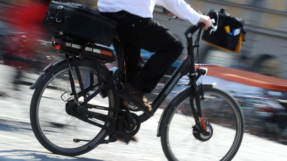 Mann radelt mit Aktenkoffer und Anzug durch die Stadt (Symbolbild)