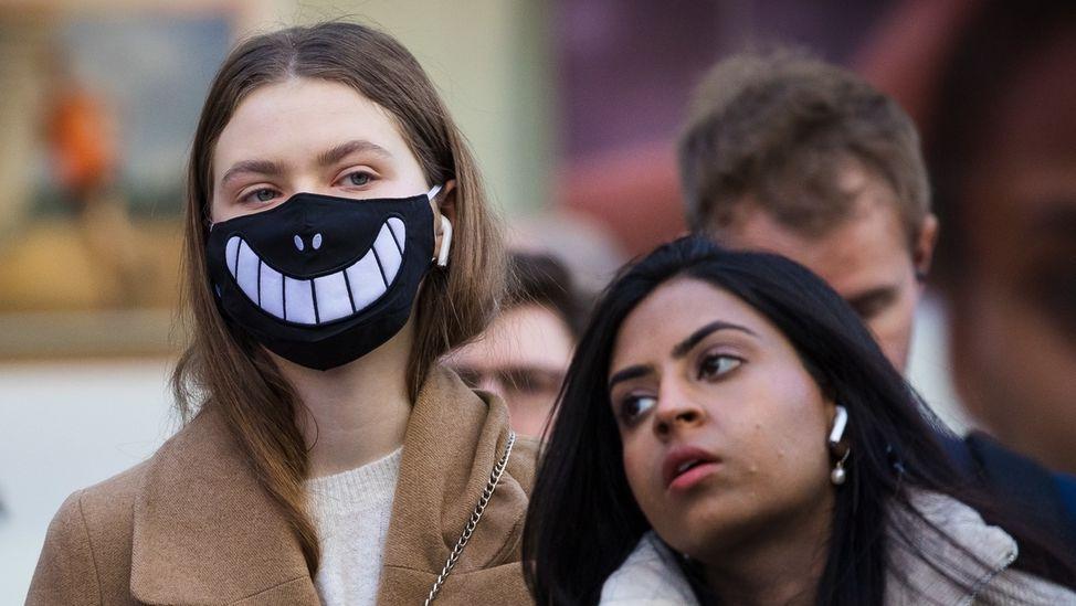 Frau in London mit Mund-Nase-Schutz.