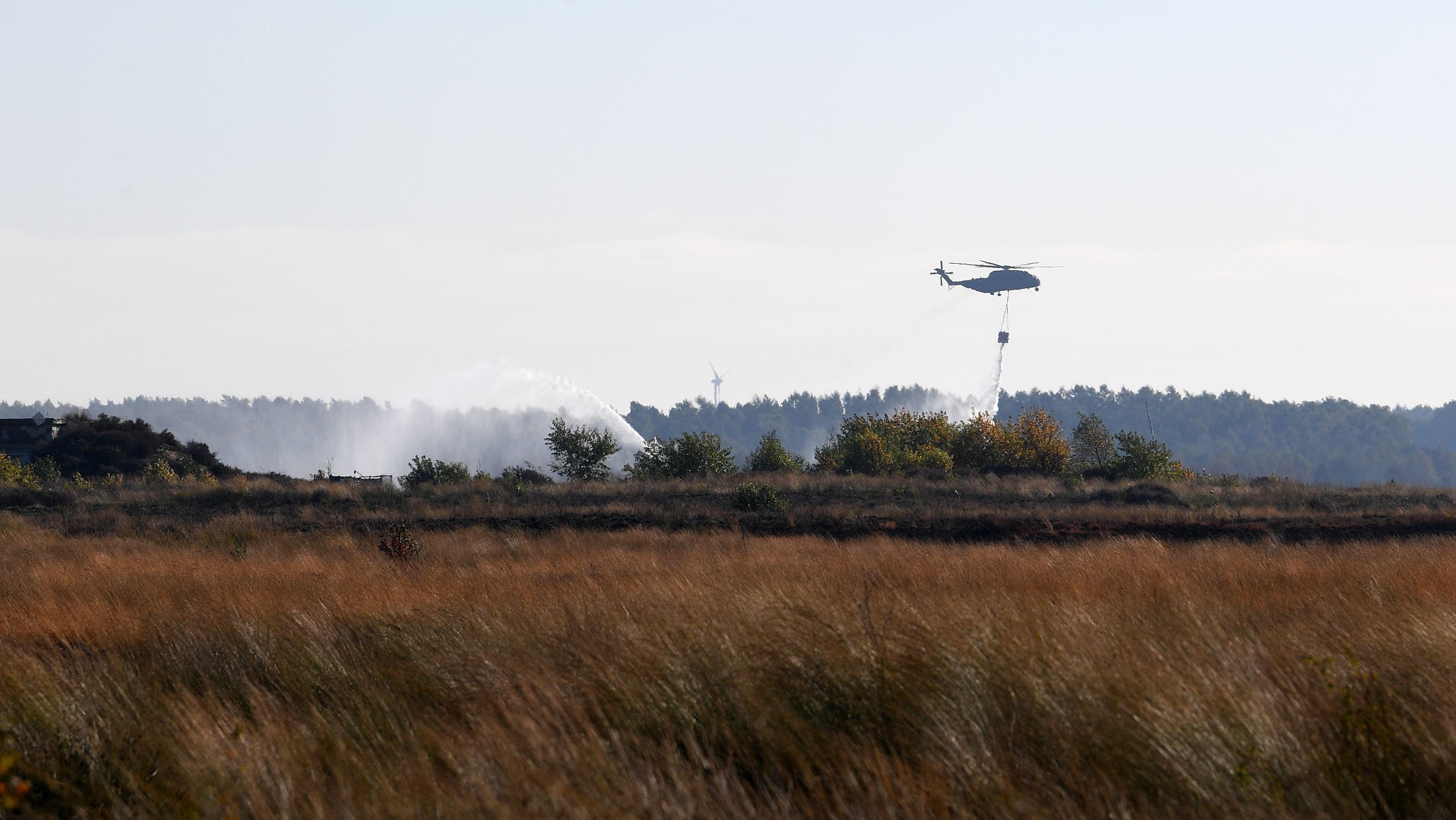 Ein Transporthubschrauber CH-53 der Bundeswehr lässt über dem Moorbrand in Meppen Löschwasser ab.