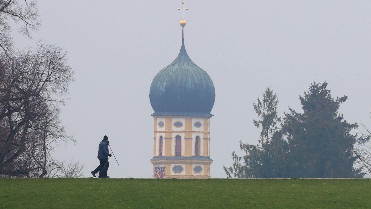 Spaziergänger gehen bei diesigem Wetter vor dem Kirchturm der Sankt Martins Kirche entlang.
