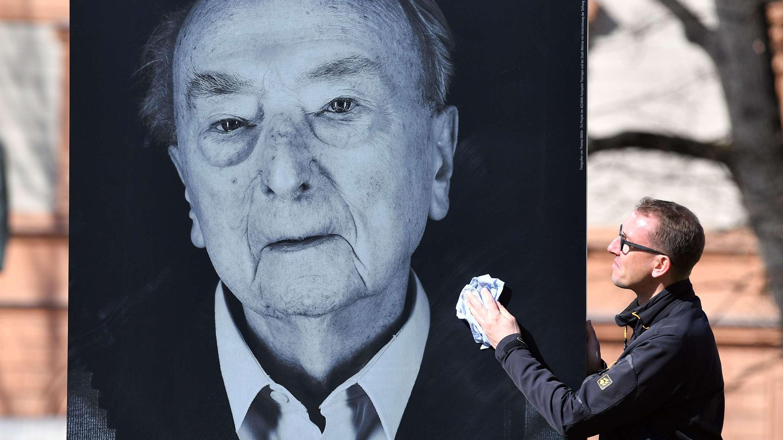 Thomas Müller neben einem Foto eines Überlebenden