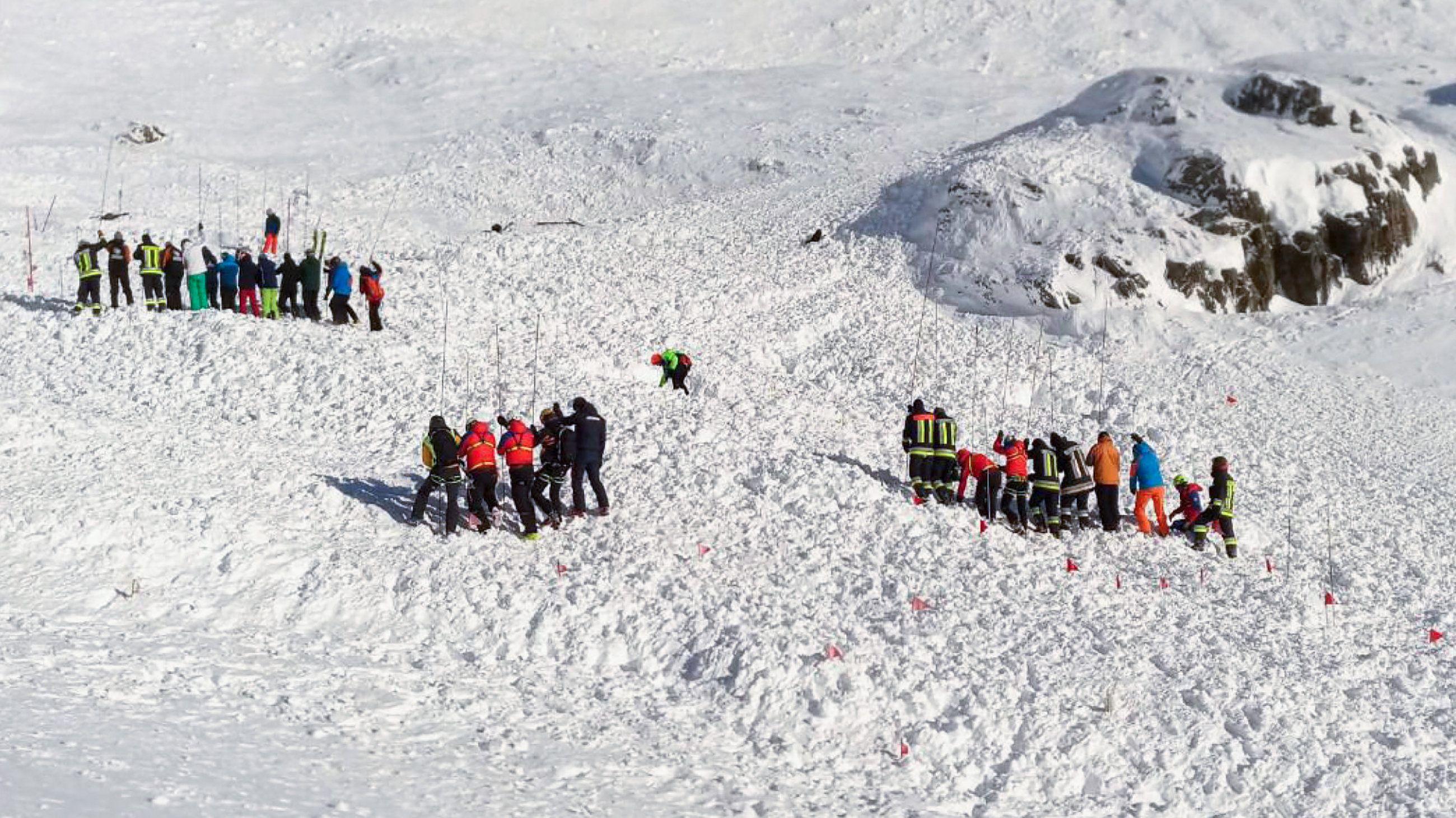 Rettungskräfte arbeiten bei einer Suchaktion nach einer Lawine auf einer Sk