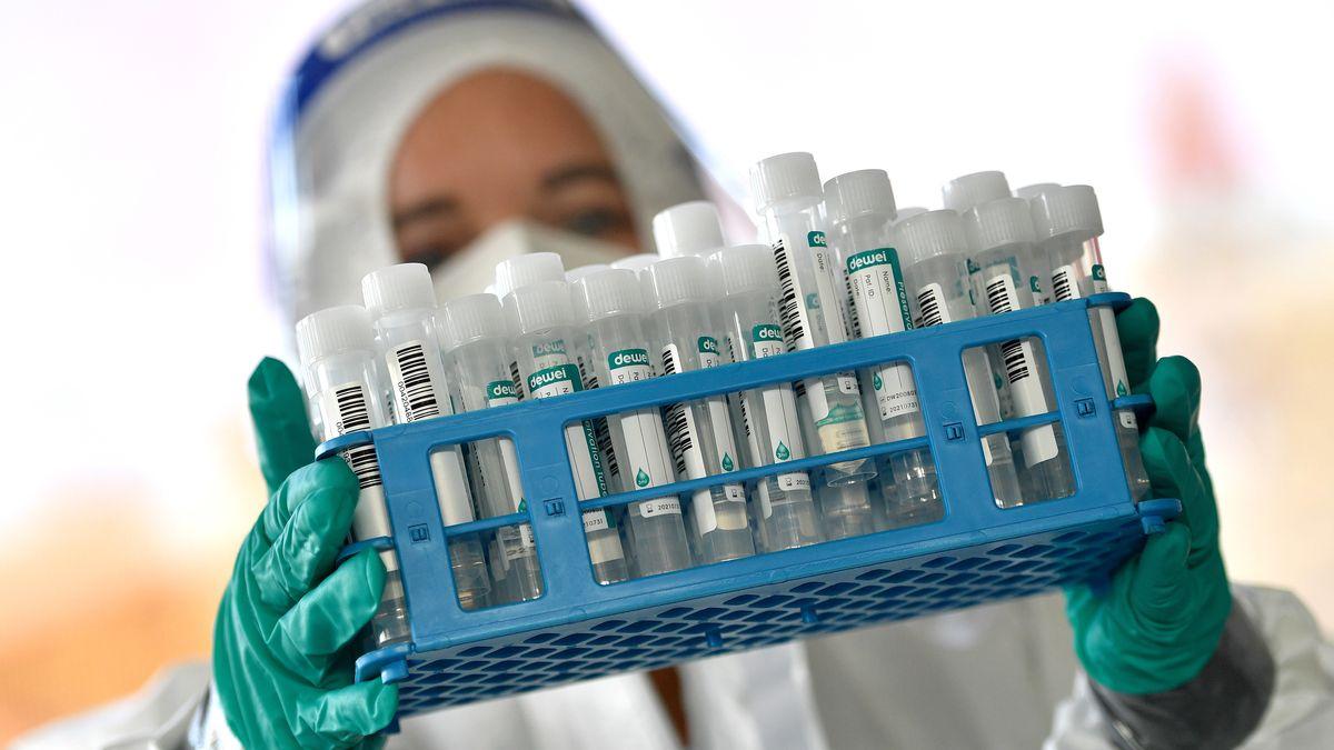 Medizinisches Personal im Schutzanzug mit einer Palette an PCR-Tests (Symbolbild).