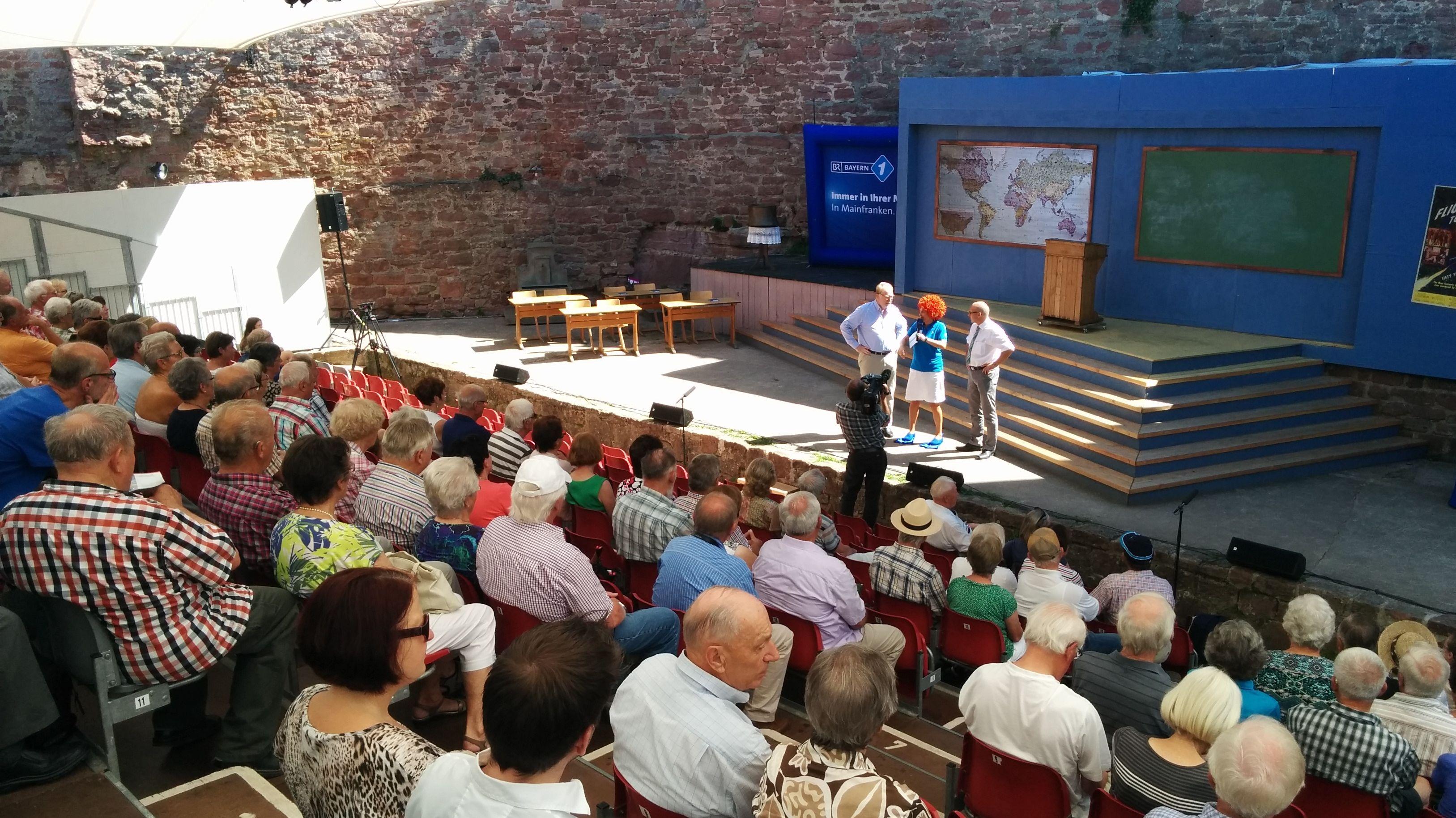 Zuschauer sitzen im Freilicht-Theater der Scherenburg-Festpiele in Gemünden.