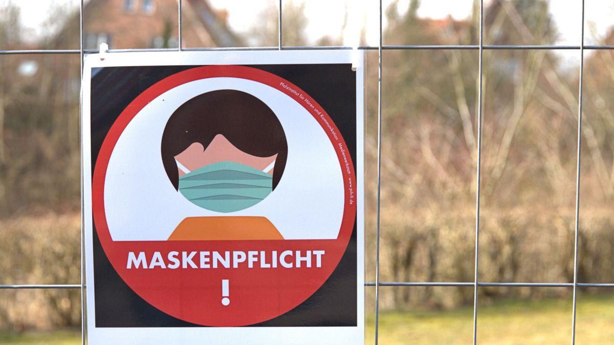 Ein Schild weist auf die Maskenpflicht hin.