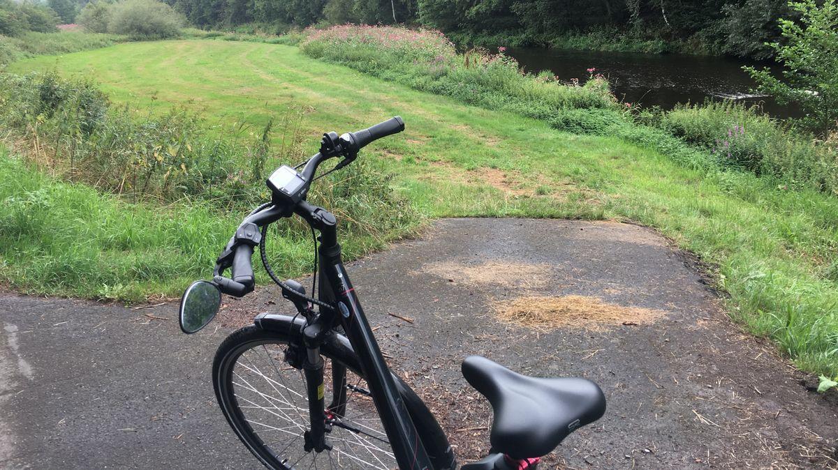 Ein schwarzes Fahrrad an einer geteerten Auffahrt zu einer gemähten Wiese, im Hintergrund ein kleiner Fluss