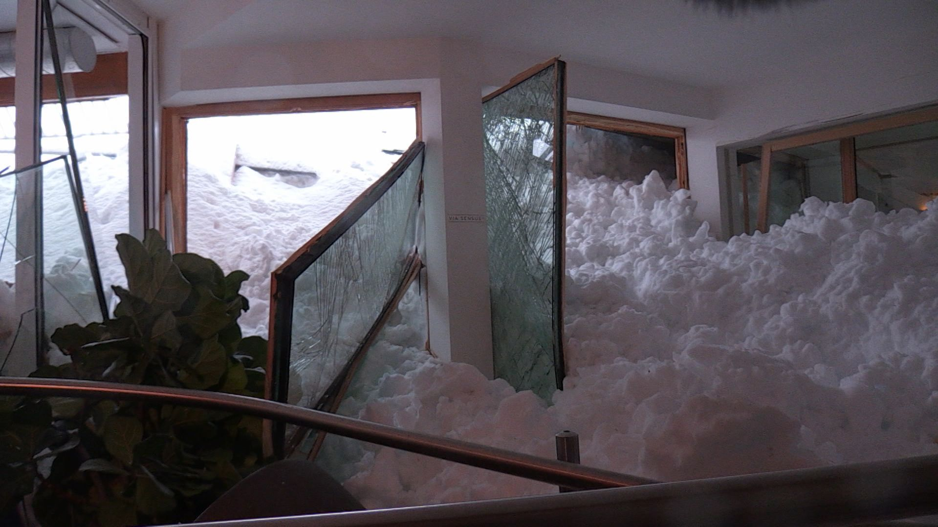 Schneemassen drücken sich durch kaputte Fenster