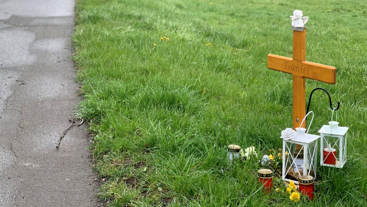 Ein Holzkreuz und Kerzen stehen in Bayreuth neben einem Radweg auf dem Boden.