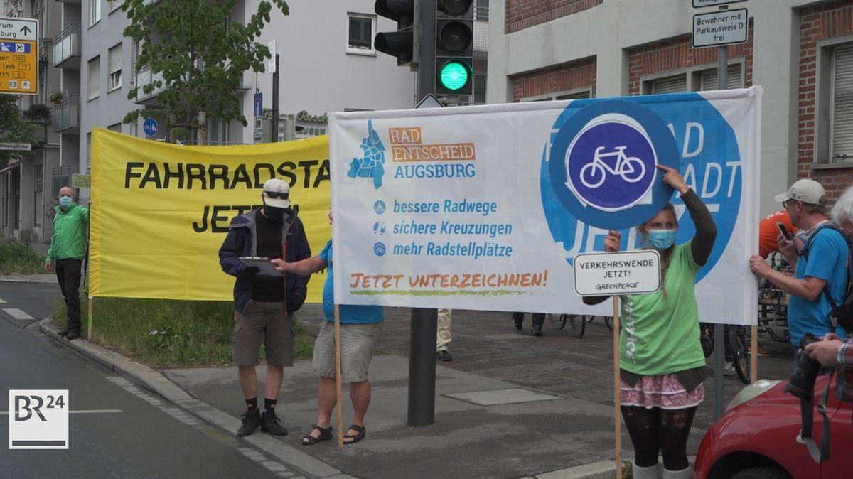 Greenpeace-Aktivisten in Augsburg halten große Plakate, die für mehr sichere Radwege werben