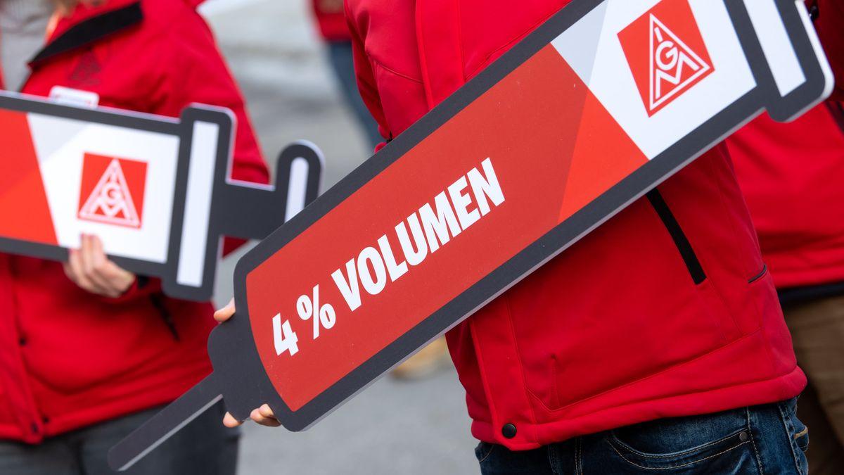 """Mitglieder der IG Metall machen vor dem Haus der bayerischen Wirtschaft mit einer Protestaktion auf ihre Forderungen aufmerksam und halten dabei eine """"Spritze"""" mit der Aufschrift """"4% Volumen"""" in den Händen."""