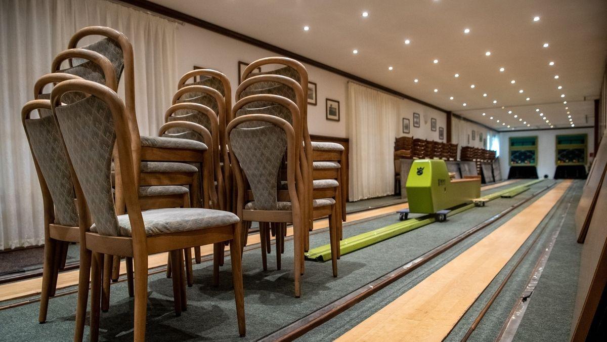 Auf der Kegelbahn einer Gaststätte werden Stühle gestapelt