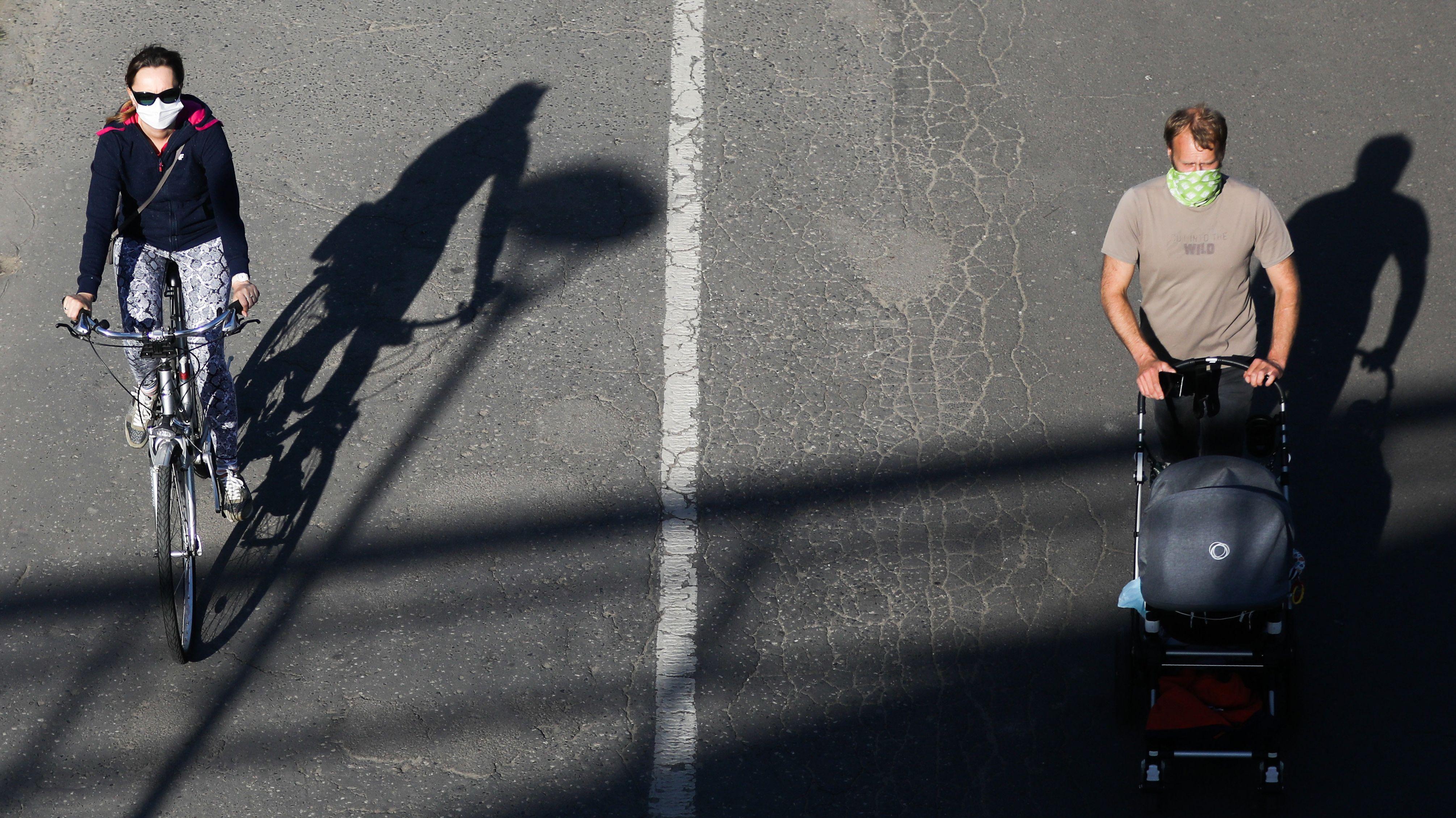 Mann mit Gesichtsmaske schiebt Kinderwagen, mehrere Meter davon entfernt fährt Frau mit Gesichtsmaske Fahrrad.