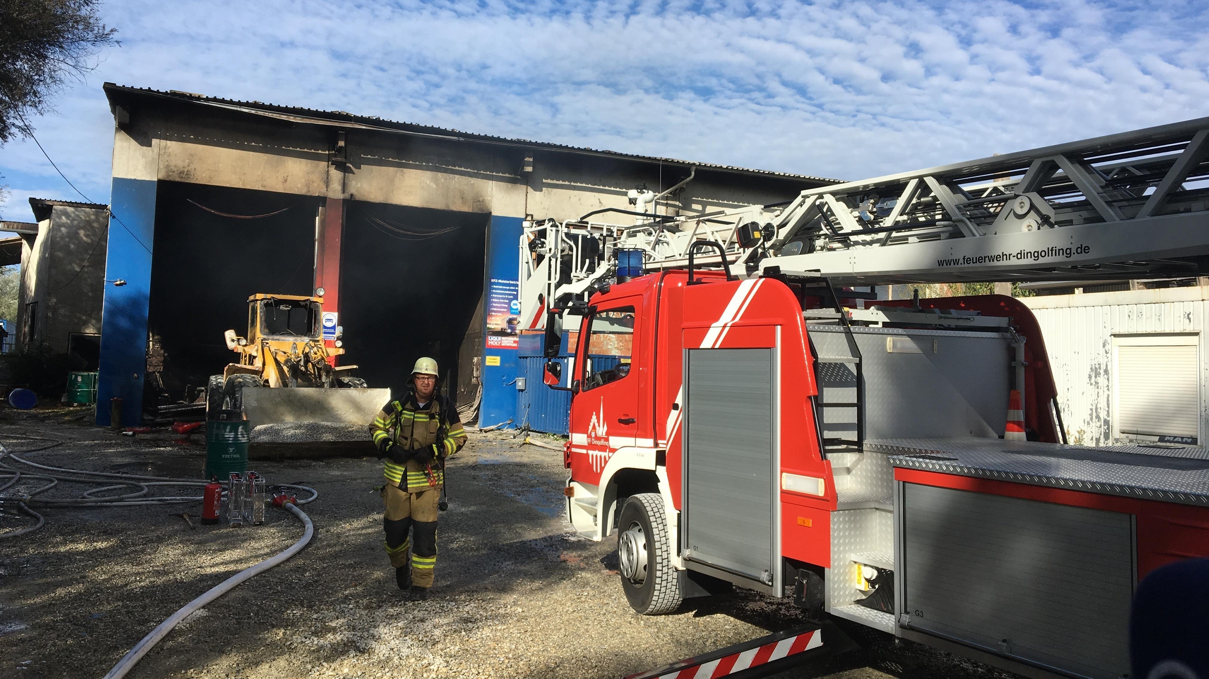 Ein Einsatzfahrzeug der Feuerwehr steht vor der brennenden Halle