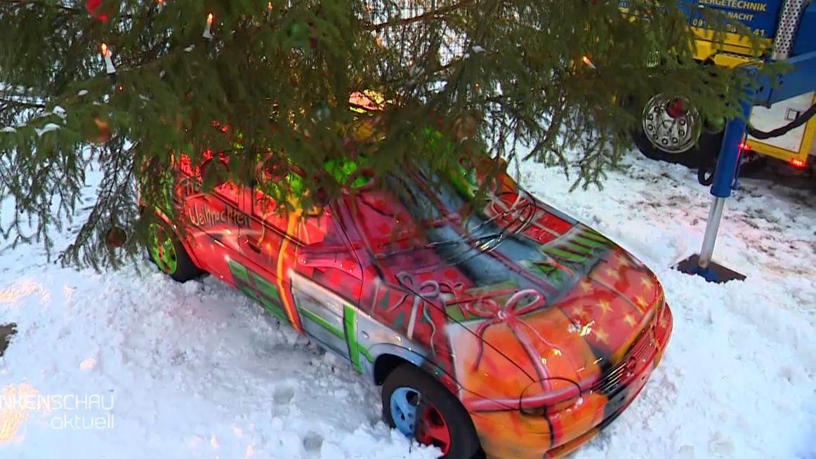 Alter Opel Corsa, bemalt in rot und orange wie ein Weihnachtspäckchen, in der Mitte ragt ein Weihnachtsbaum empor.