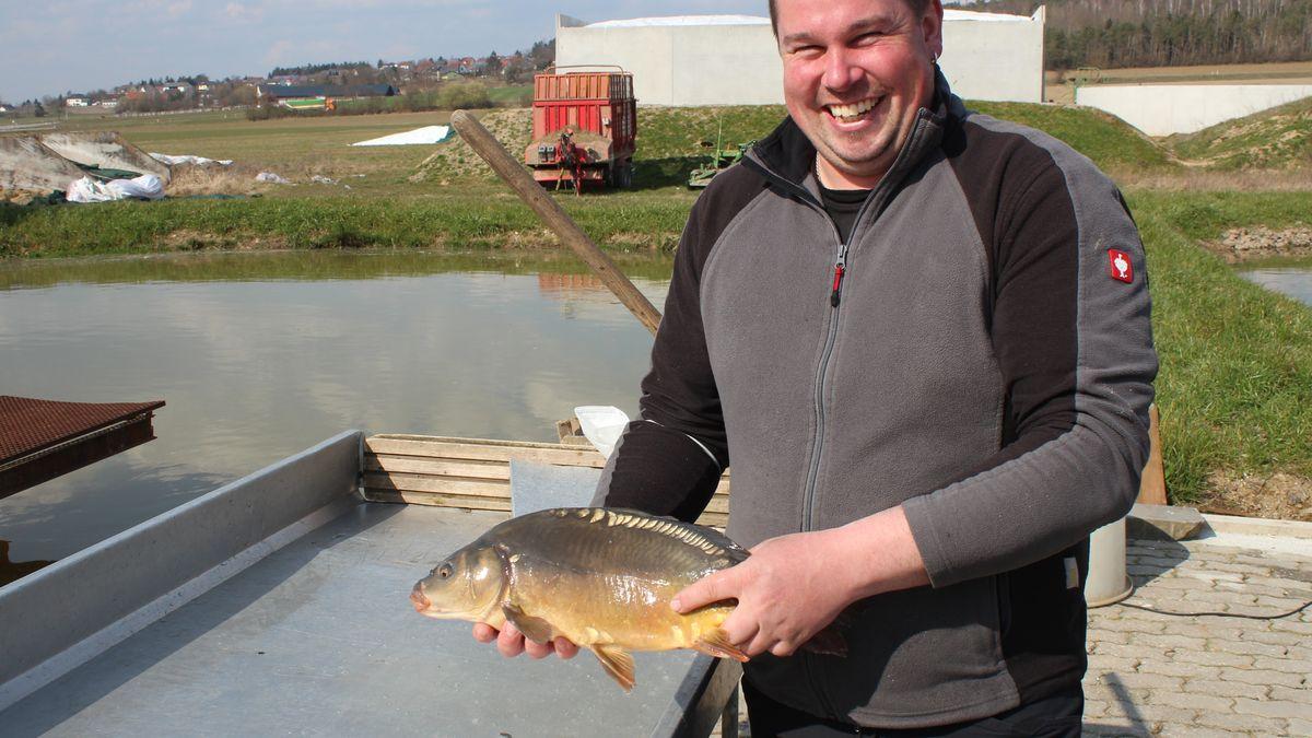 Johannes Schießl hält einen Fisch in den Händen und lächelt.