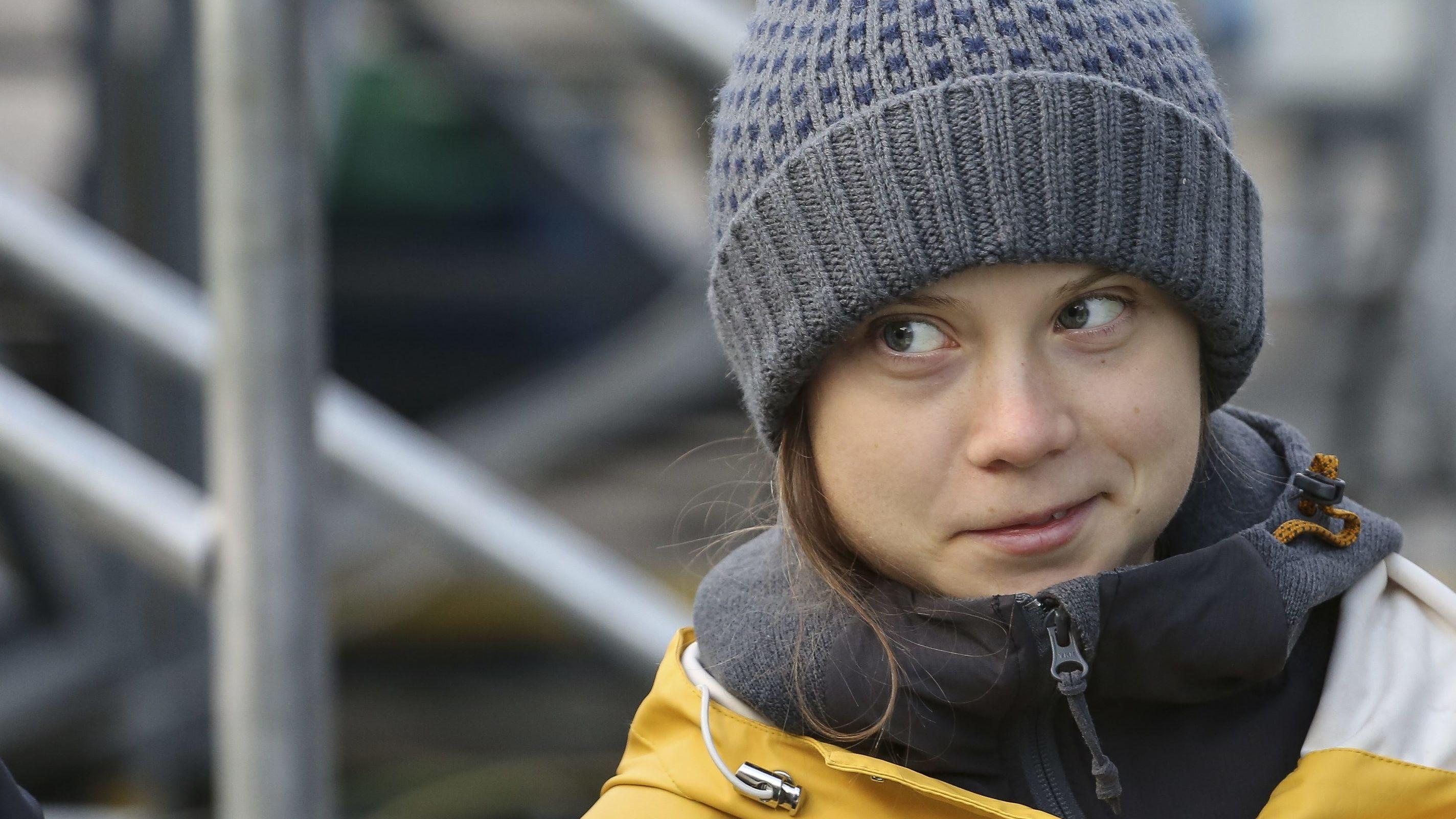 """Demo von """"Fridays for Future"""" in Turin im Dezember 2019: Greta Thunberg blickt, mit gelbem Regenmantel und grauer Mütze, spöttisch lächelnd zur Seite"""