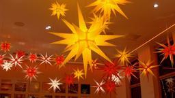 Zwei Dutzend hell leuchtende Herrnhuter Sterne an der Decke eines Raums. | Bild:BR / Sabine Barth