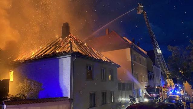 Ein Feuerwehrmann löscht von der Feuerwehrleiter aus den brennenden Dachstuhl, aus dem Flammen schlagen.