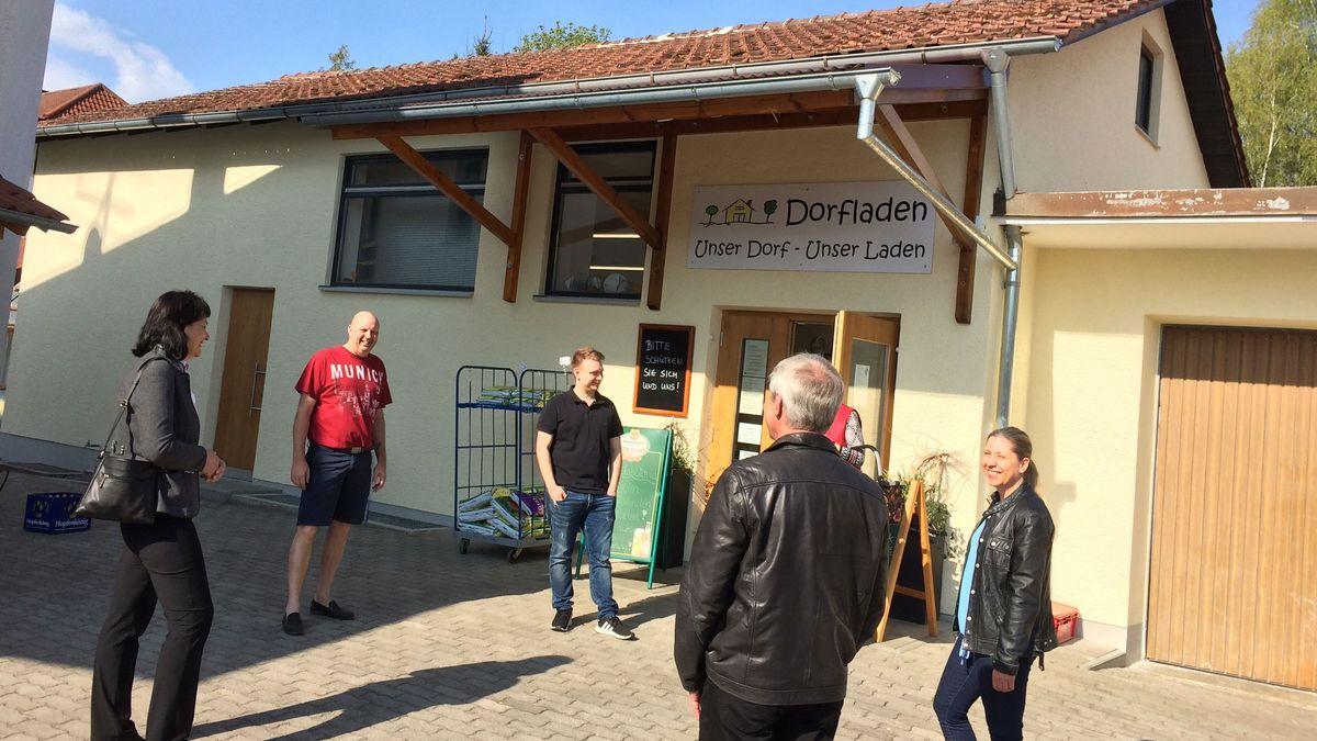 Kunden begegnen sich vor dem Dorfladen und ratschen mit Abstand zueinander beim Warten