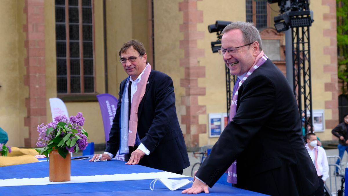 """Der katholische Bischof Georg Bätzing (vorne) und sein evangelischer Kollege Volker Jung bei der Kunstinstallation """"Ein Tisch"""" in Frankfurt."""