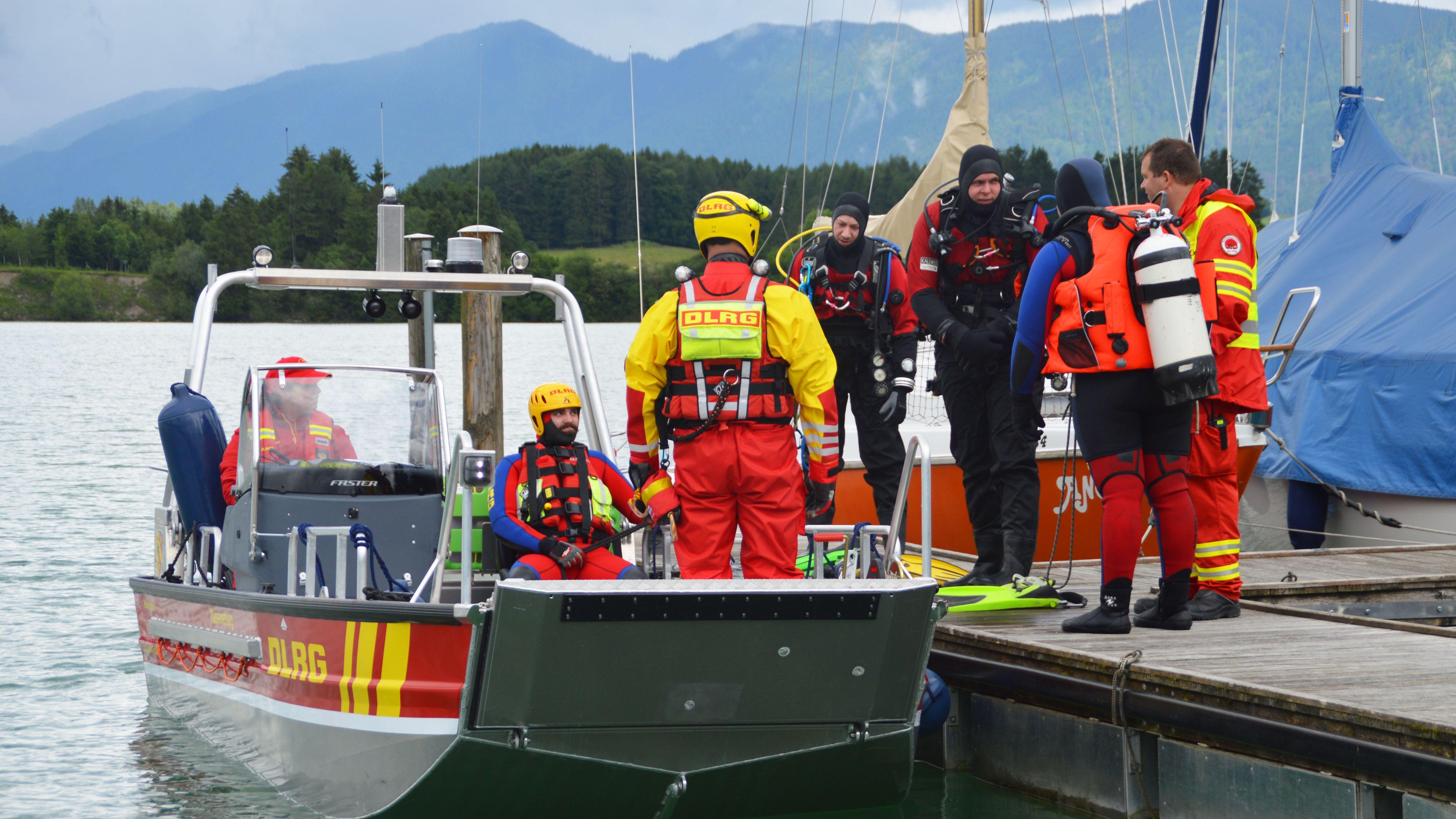 Wasserretter der DLRG in einem Rettungsboot, das an einem Steg liegt; auf dem Steg weitere Retter.