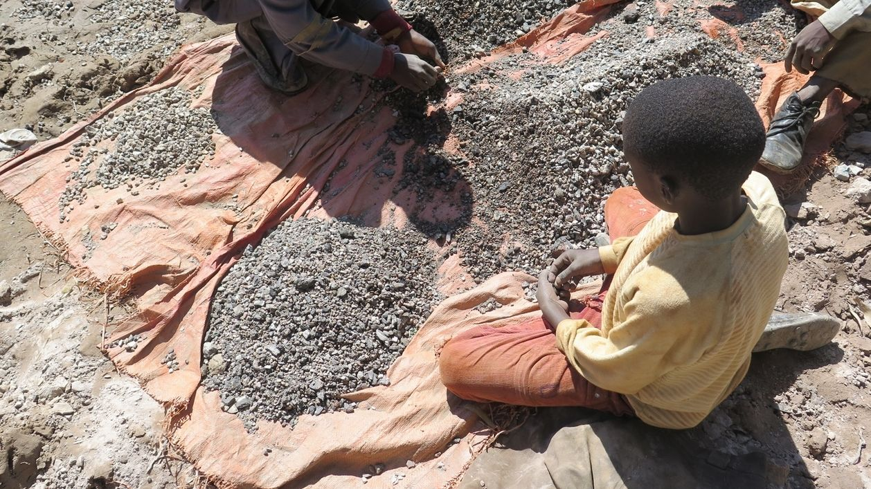 Kind, das in einer Kobaltmine arbeitet, sitzt auf dem Boden