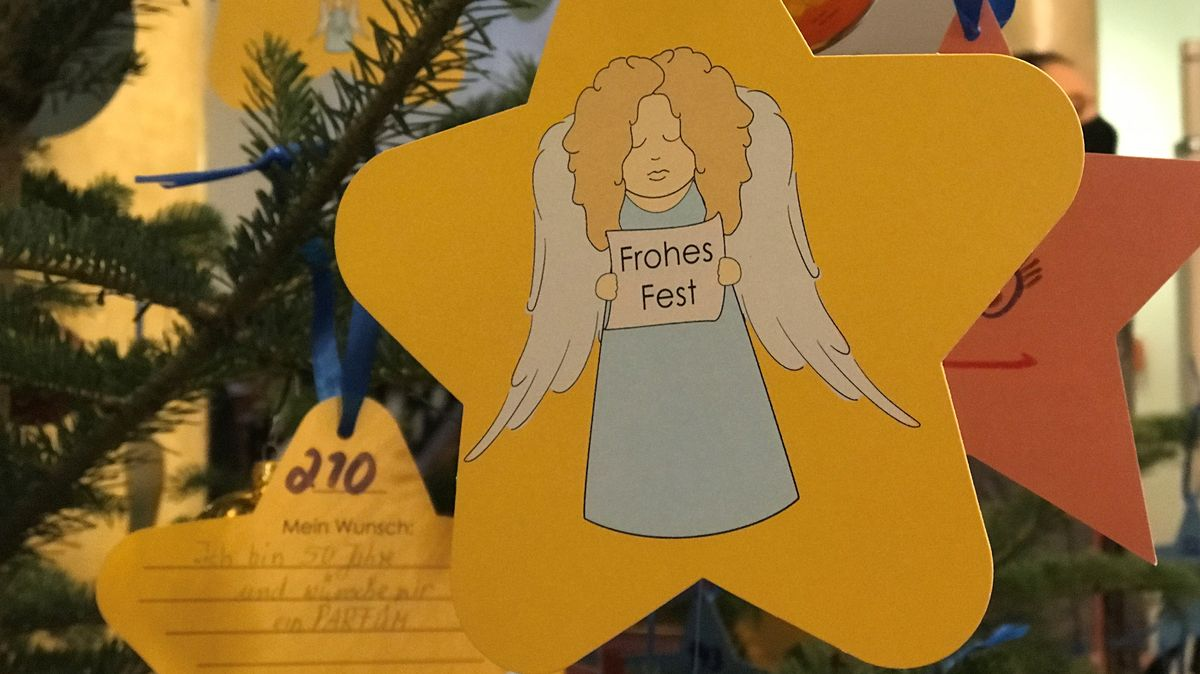Gelbe Karten hängen an einem Christbaum, auf einer Karte ist zu lesen: ich bin 50 Jahre und wünsche mit ein Parfüm.