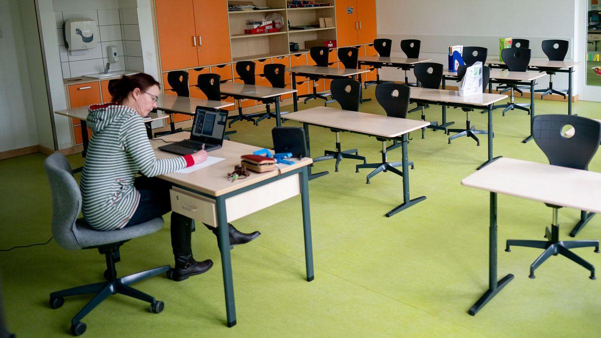 Eine Lehrerin macht im leeren Klassenzimmer eine Videokonferenz mit ihren Schülern