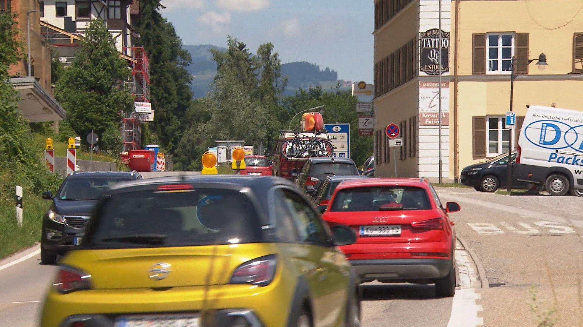 Zahlreiche Autos fahren durch eine Ortschaft in Tirol.