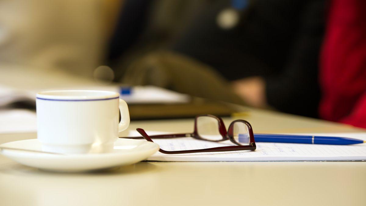 Eine Tasse, eine Brille und ein Block mit Stift auf einem Tisch während einer Sitzung