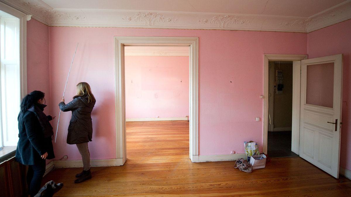 Interessenten messen bei einer Wohnungsbesichtigung eine Mietwohnung aus.