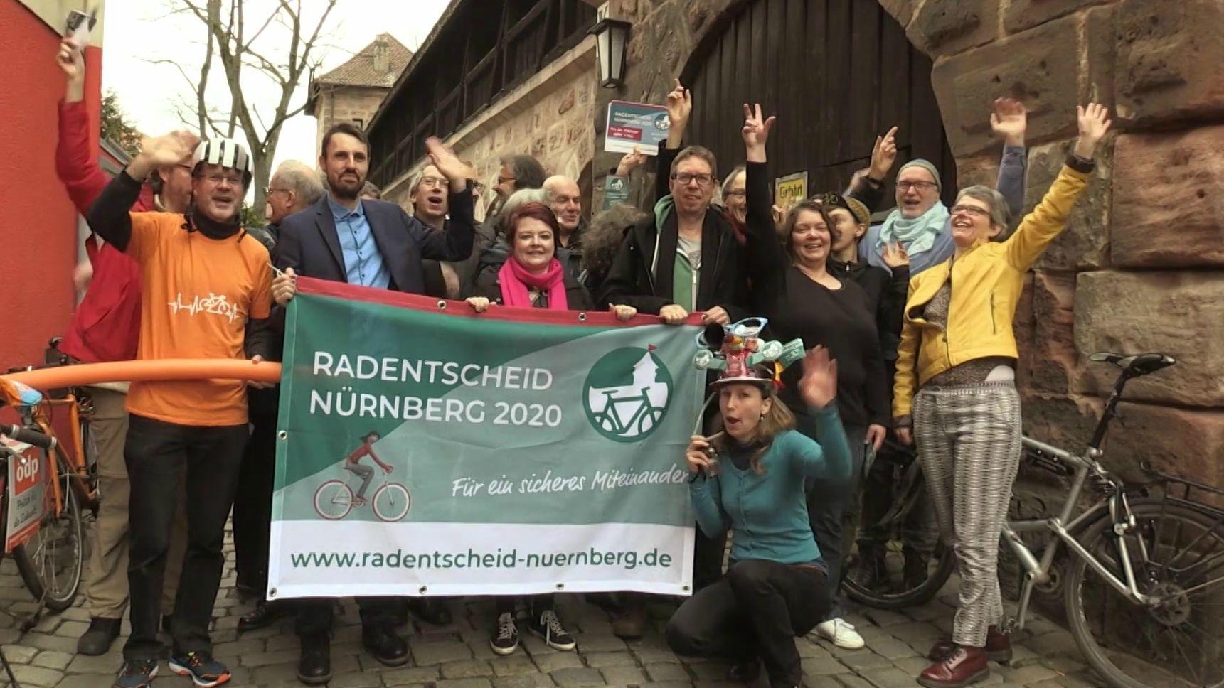 Organisatoren des Nürnberger Radentscheids zeigen das Transparent zum Radentscheid