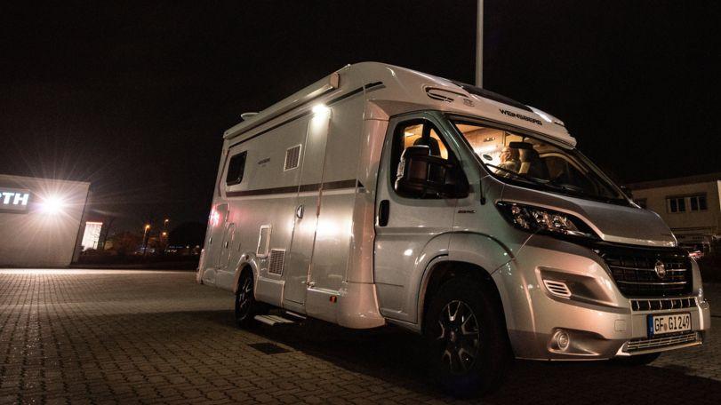 Ein Wohnmobil der Marke Fiat auf einem Parkplatz bei Nacht