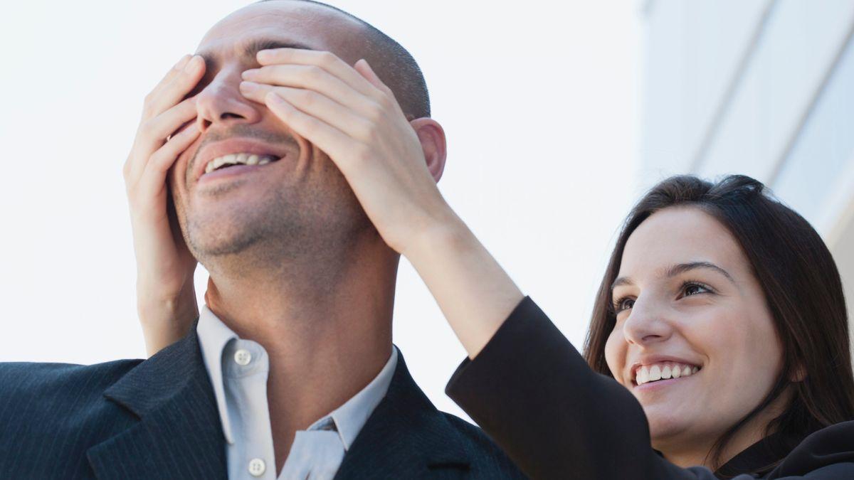 Eine junge Frau hält ihrem Partner von hinten die Augen zu.