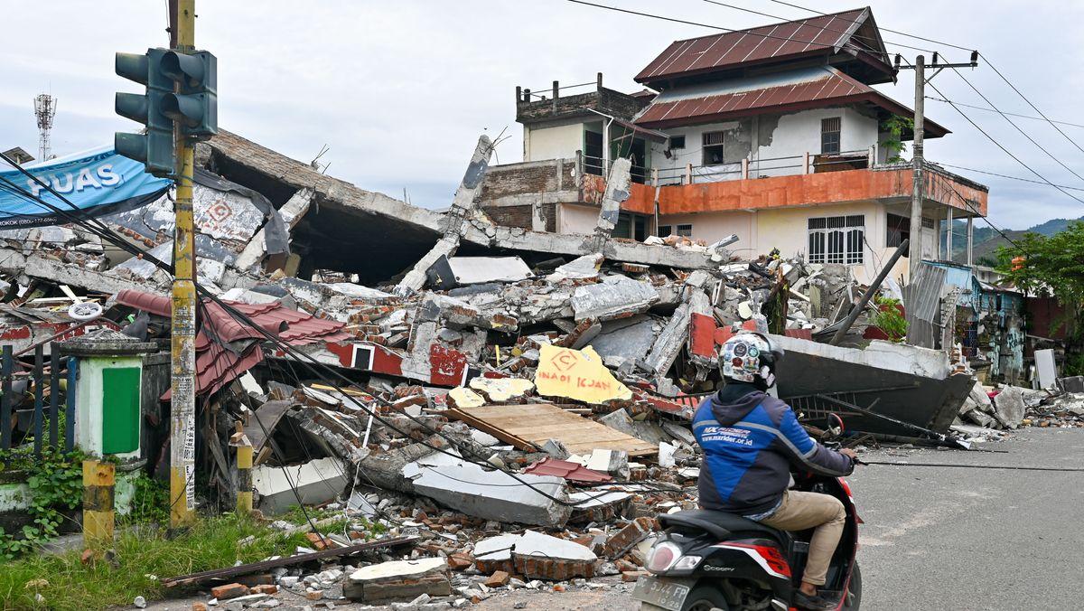 Mamuju, West-Sulawesi, Indonesien: Ein Autofahrer fährt an einem beschädigten Gebäude vorbei.