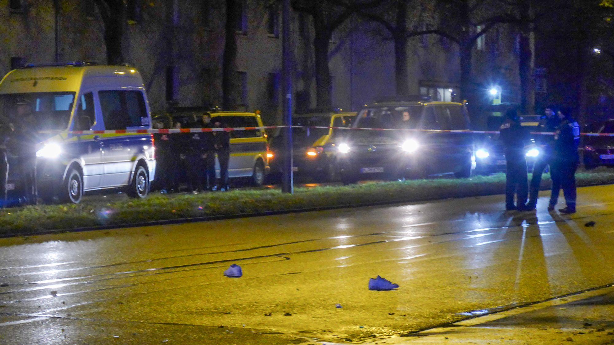 Sneakers liegen nach einem Unfall auf der Fürstenrieder Straße in Laim, im Hintergrund Polizeiautos und -beamte.