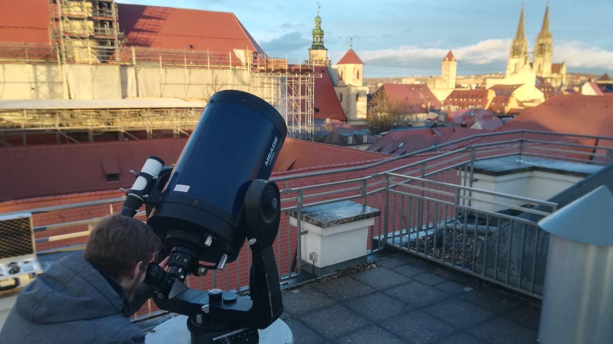 Ein Besucher der Regensburger Sternwarte schaut durch ein Teleskop.