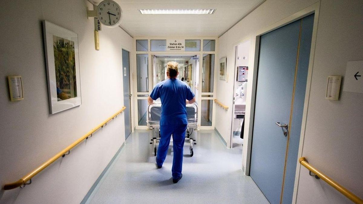 Ein Pfleger schiebt ein Krankenbett über den Flur eines Krankenhauses.