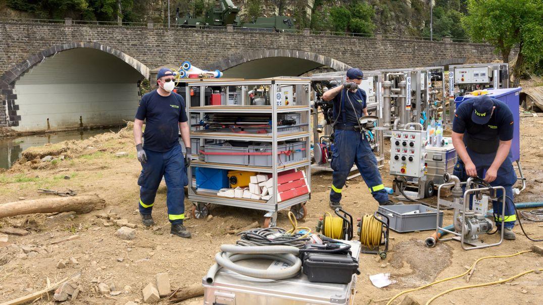 THW-Helfer bauen eine Trinkwasseraufbereitungsanlage ab, um sie auf einem höher liegenden Platz wiederaufzubauen.