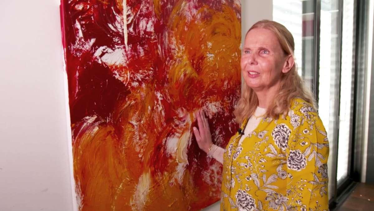"""Malerin Claudia Stiglmayr-Keshishzadeh steht vor einem ihrer Bilder und tastet es mit den Händen ab. Das Bild zeigt rote und orangene Muster. Es trägt den Titel """"Summerfeelings"""""""