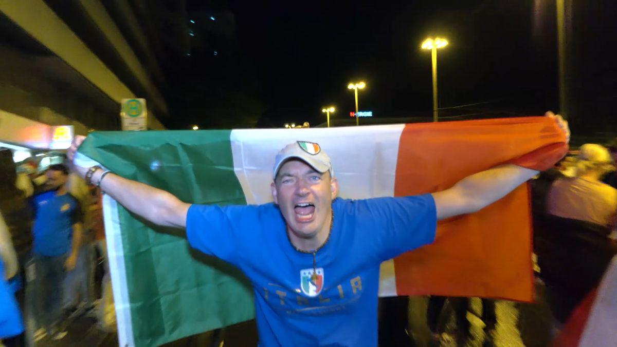 Ein italienischer Fußballfan hält jubelnd eine grün-weiß-rote Italienfahne über sich.