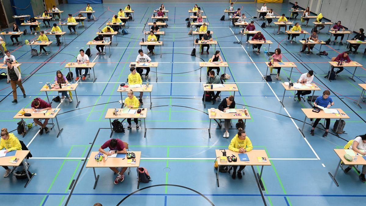 Schüler und Schülerinnen sitzen während einer Abiturprüfung 2020 mit dem vorgeschriebenen Abstand zueinander in einer Sporthalle.