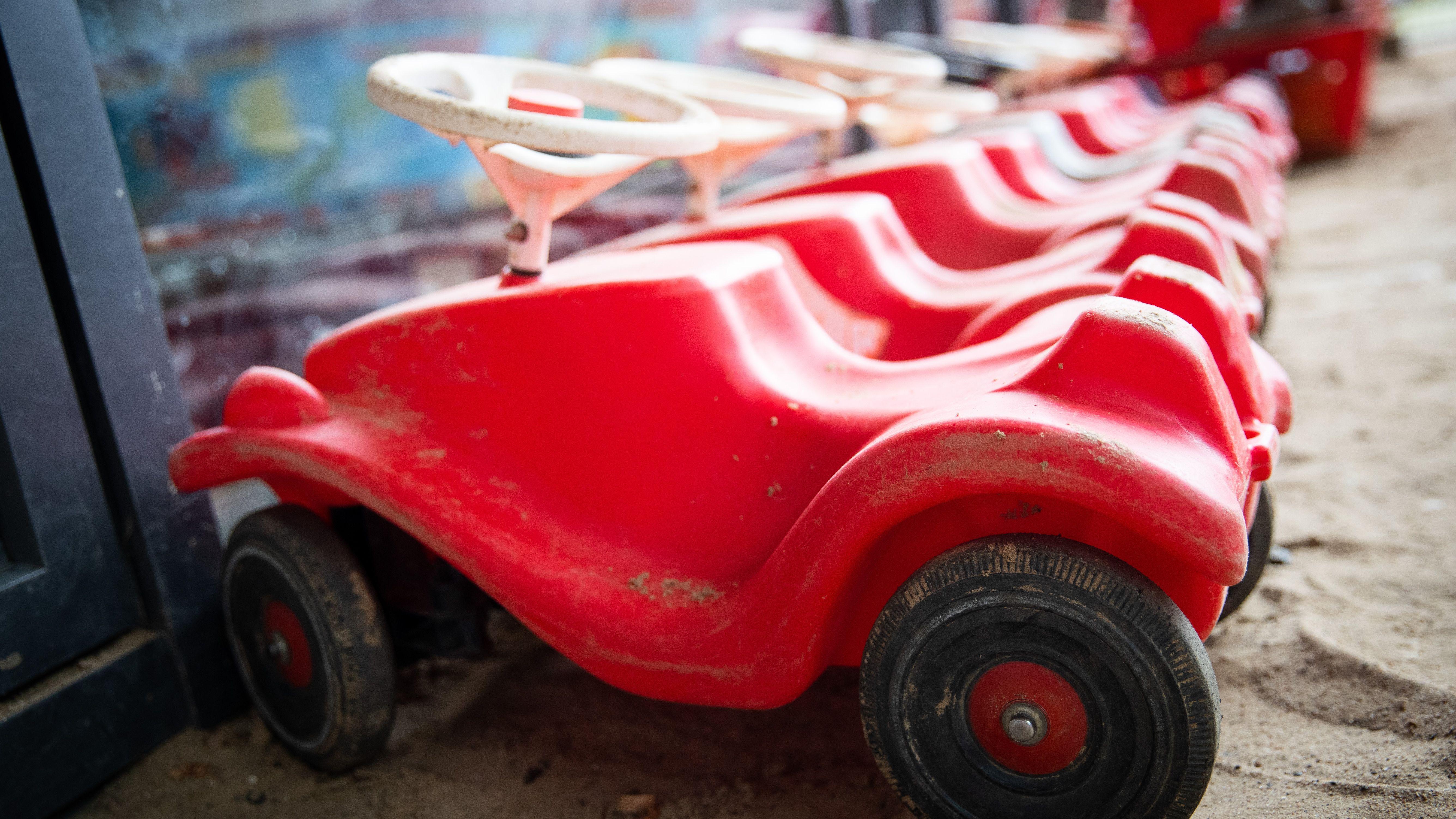 Mehrere Bobbycars stehen nebeneinander aufgereiht in einem Kindergarten (Symbolbild)