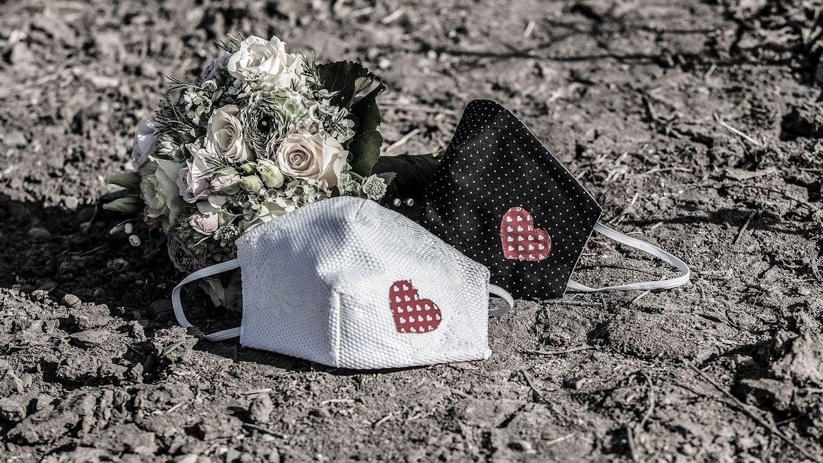 Zwei Mund-Nasen-Masken mit aufgenähtem Herz liegen neben einem Brautstrauß (Symbolbild)